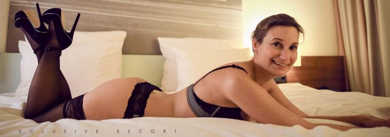 Celine von Xclusive Escort Hamburg bezaubernd lächelnd im Bett