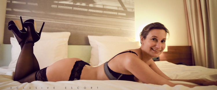 Escort Hamburg Dame Celine von Xcluisve erwartungsvoll im Bett liegend