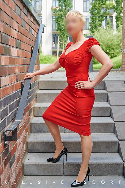 Escort Hamburg Dame Lea in elegantem rotem Kleid