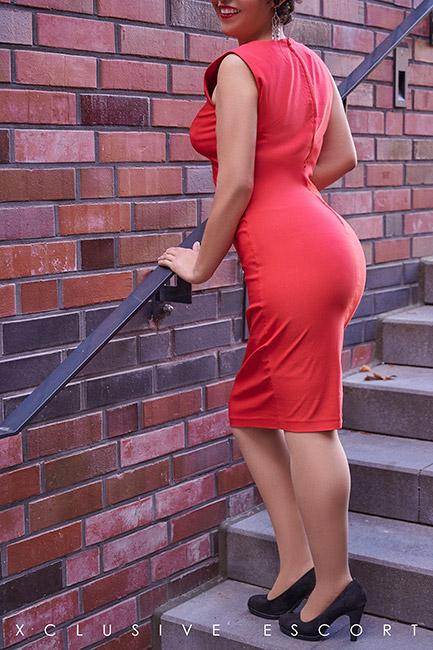 Escort Dame Maze vom Escort Berlin in elegantem roten Kleid.
